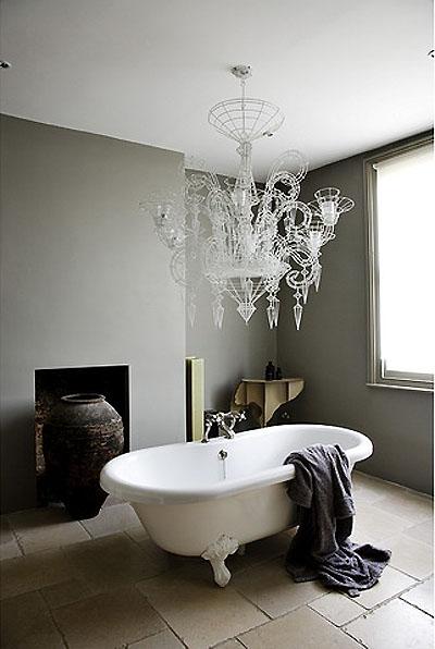 Baño vintage con lámpara chandelier de diseño y chimenea. Foto Morten Holtum